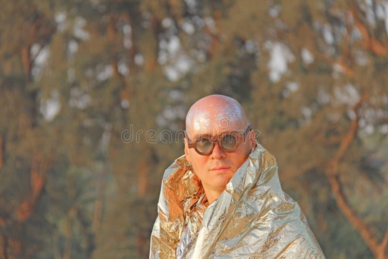 Un homme chauve et bel, un phénomène dans un cap d'or ou vêtements et photo libre de droits