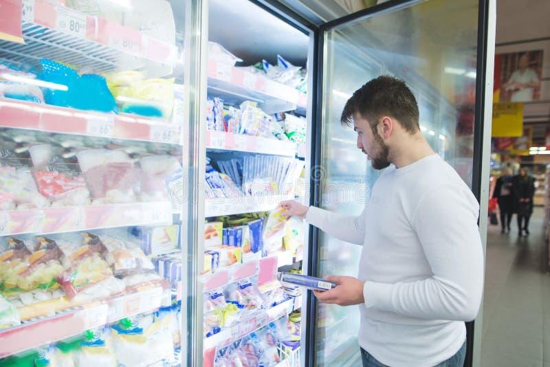 Un homme choisit les aliments surgelés des étagères dans un réfrigérateur dans un supermarché Un homme achète des produits dans l photo stock