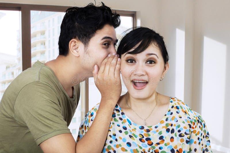 Un homme chuchotant un secret à son amie photo libre de droits
