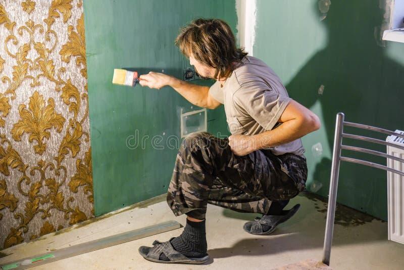 Un homme colle des papiers peints images stock