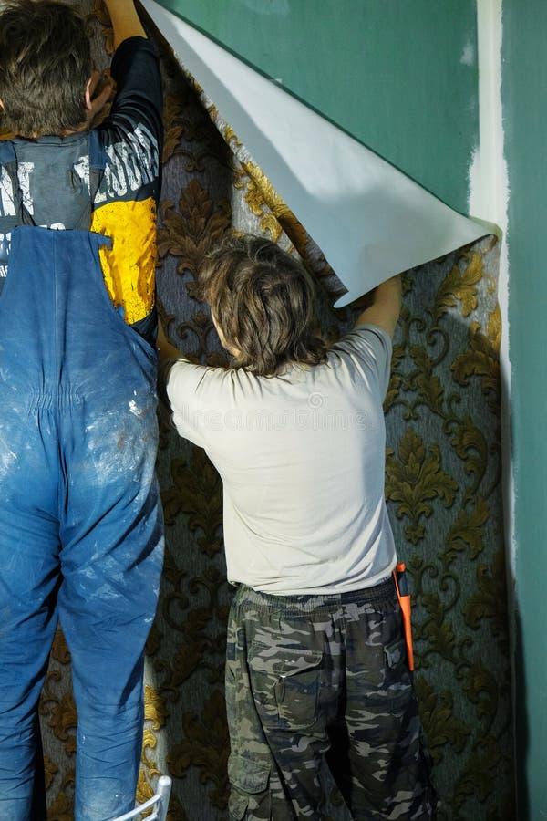 Un homme colle des papiers peints images libres de droits