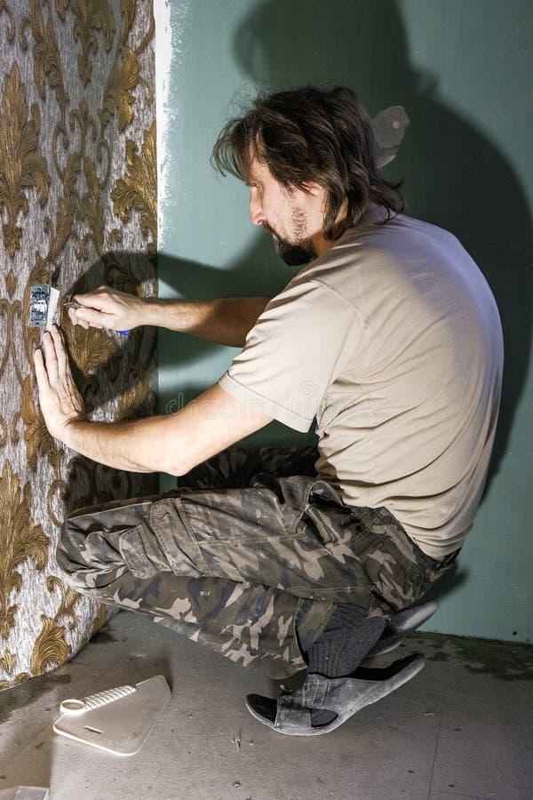 Un homme colle des papiers peints image libre de droits