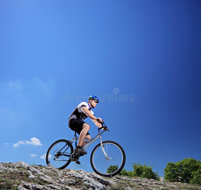 Un homme conduisant un vélo de montagne sur une pente images stock