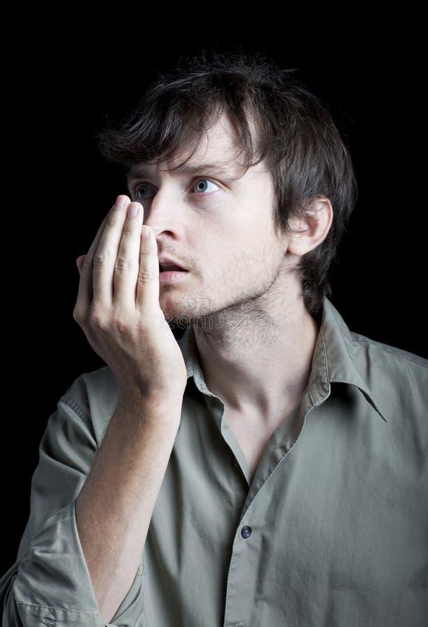 Un homme contrôlant son mauvais souffle image stock