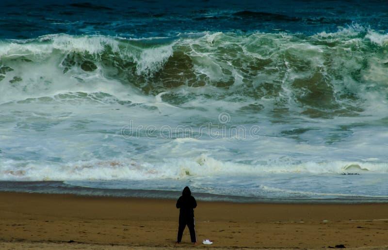 Un homme contre la fureur de l'océan pacifique photographie stock libre de droits