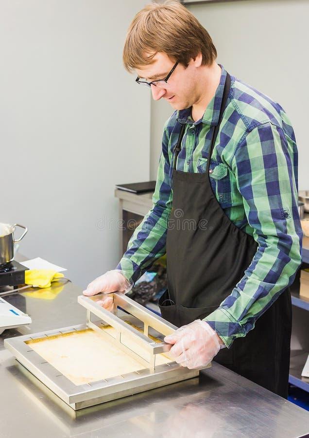 Un homme a coupé la pâtisserie de napoléon de gâteau images stock