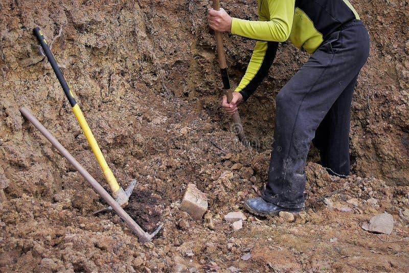 Un homme creusant un trou avec une pelle pour le projet images libres de droits