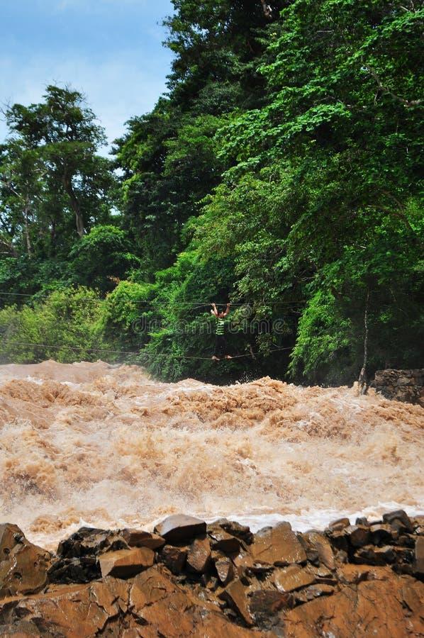Un homme croise les cascades d'automnes du Mékong Khone Phapheng au Laos du sud sur des câbles images libres de droits