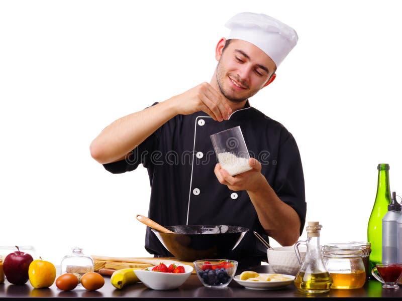 Un homme, un cuisinier, se tient dans la cuisine avec des puces de noix de coco, pendant la cuisson images libres de droits