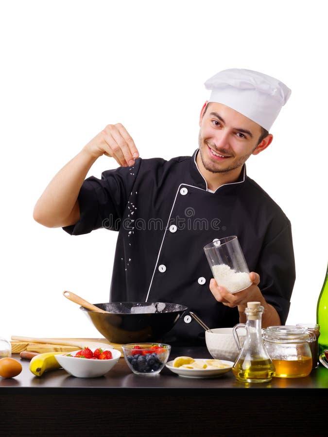 Un homme, un cuisinier, se tient dans la cuisine avec des puces de noix de coco, pendant la cuisson photos libres de droits