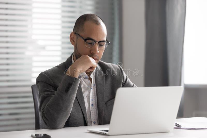 Un homme d'affaires afro-américain réfléchi utilisant un ordinateur portable, réfléchir à un projet photo stock