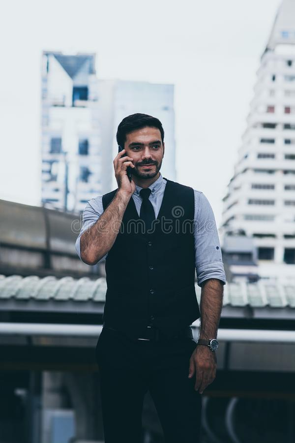 Un homme d'affaires appelle quelqu'un en utilisant un téléphone mobile photo stock