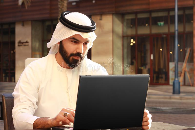 Un homme d'affaires arabe bel Using Laptop Technology et homme arabe de port d'affaires de robe traditionnelle des EAU images stock