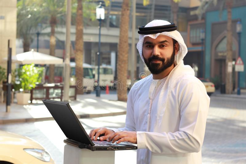 Un homme d'affaires arabe bel Using Laptop Technology et homme arabe de port d'affaires de robe traditionnelle des EAU photo stock