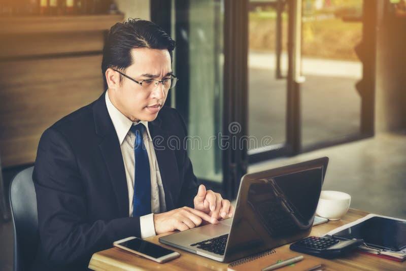 Un homme d'affaires asiatique est soucieux au sujet des affaires avec l'informat photo libre de droits