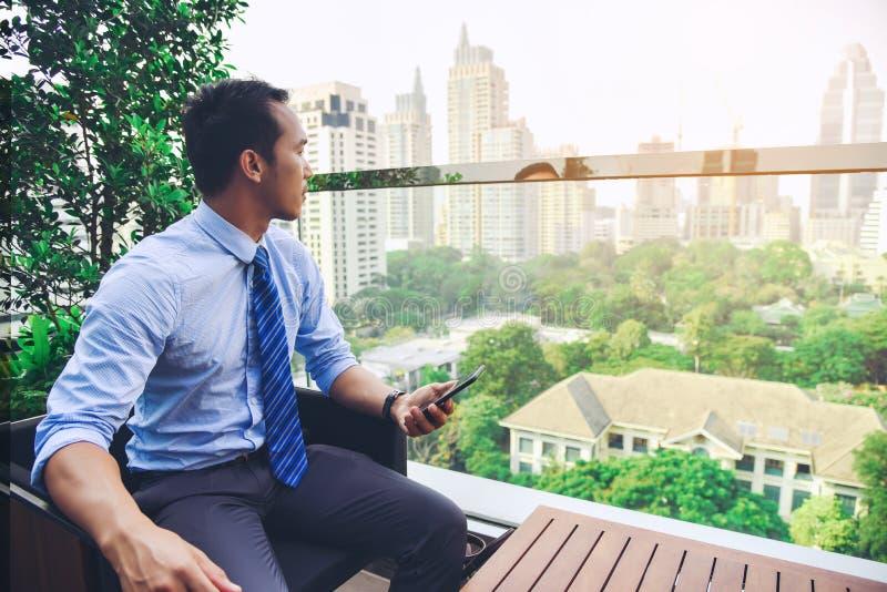 Un homme d'affaires asiatique observe la croissance du grand thro de ville images stock