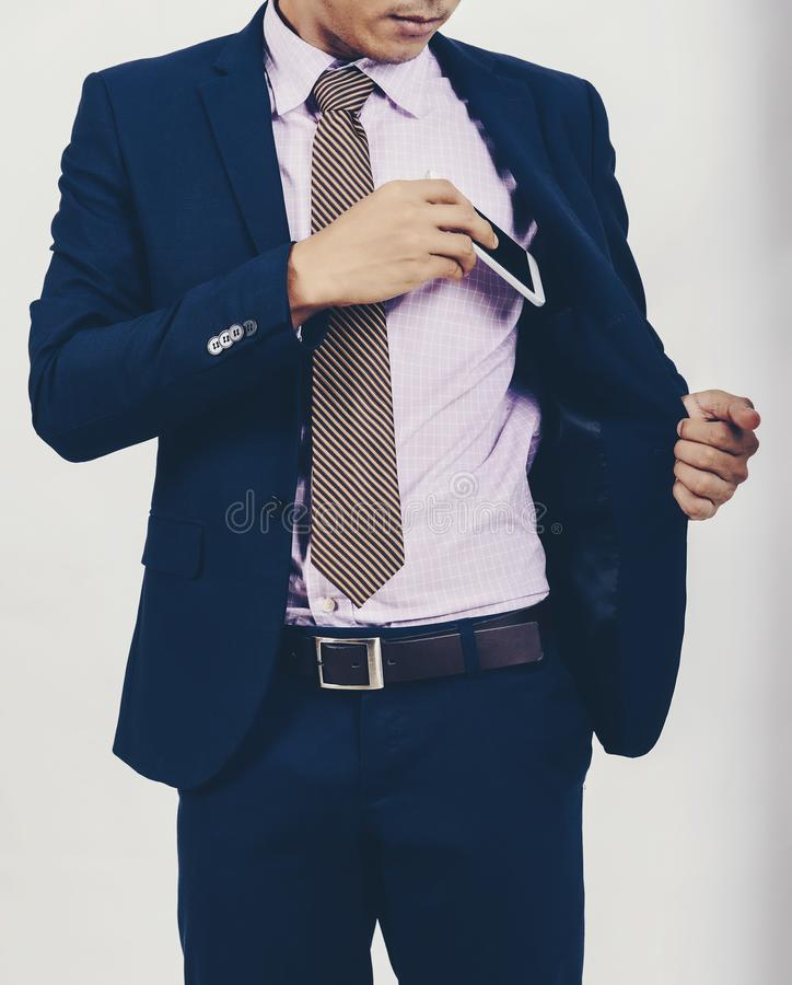 Un homme d'affaires asiatique prend un smartphone de sa poche photographie stock