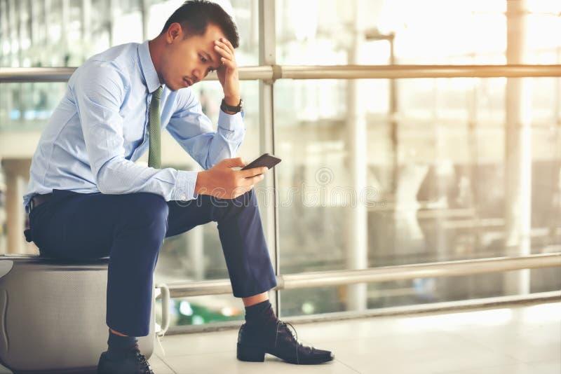 Un homme d'affaires asiatique s'assied sur son bagage Il a été soumis à une contrainte image stock