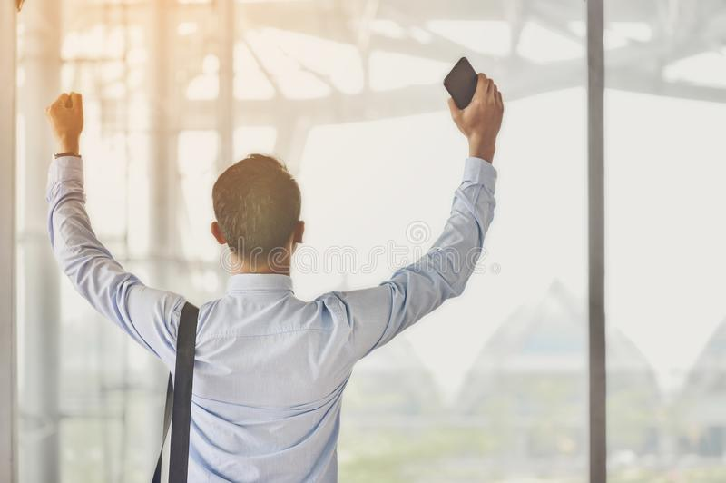 Un homme d'affaires asiatique tenant un smartphone tient sa main sur le cong photo stock