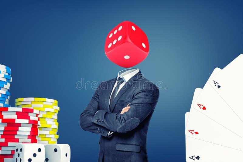 Un homme d'affaires avec les bras pliés se tient avec une grande matrice de casino au lieu de sa tête image libre de droits