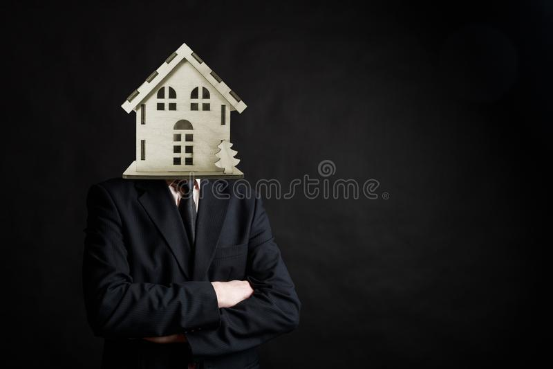 Un homme d'affaires avec woden la maison au lieu de ses supports principaux avec les bras pliés sur le fond noir photo libre de droits