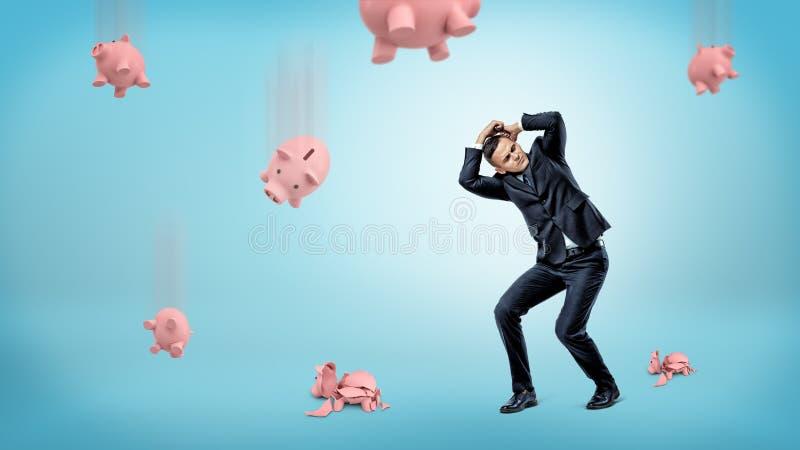 Un homme d'affaires cache sa tête de beaucoup de tirelires qui tombent vers le bas et fendent au plancher image stock