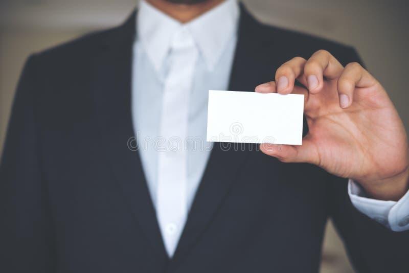 Un homme d'affaires dans la chemise blanche et le costume gris montrant la carte de visite professionnelle de visite vide images libres de droits