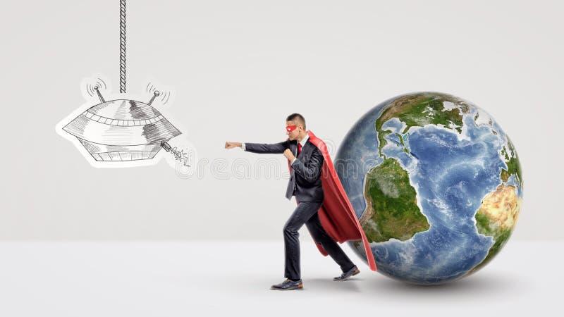 Un homme d'affaires de super héros combattant un dessin de papier d'un UFO tandis que derrière lui supports un petit globe de la  photos libres de droits