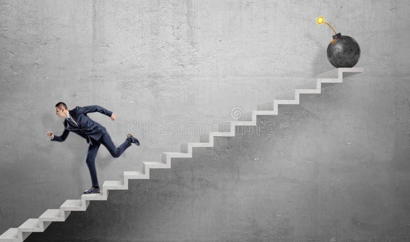 Un homme d'affaires effrayé descendant en courant les escaliers concrets gris à partir d'une grande bombe de fer avec un fusible  photos libres de droits