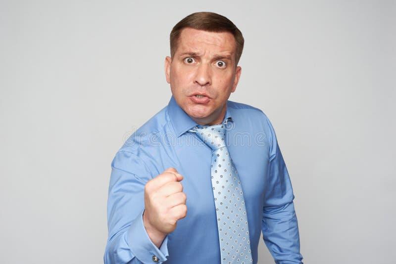 Un homme d'affaires en colère isolé sur le sol gris image libre de droits