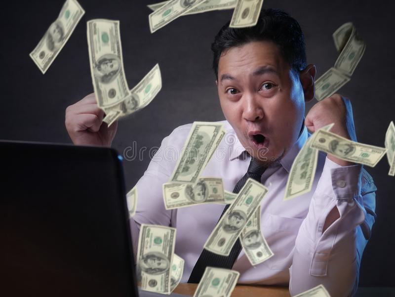 Un homme d'affaires enthousiasmé de voir de l'argent de son ordinateur portable photo stock