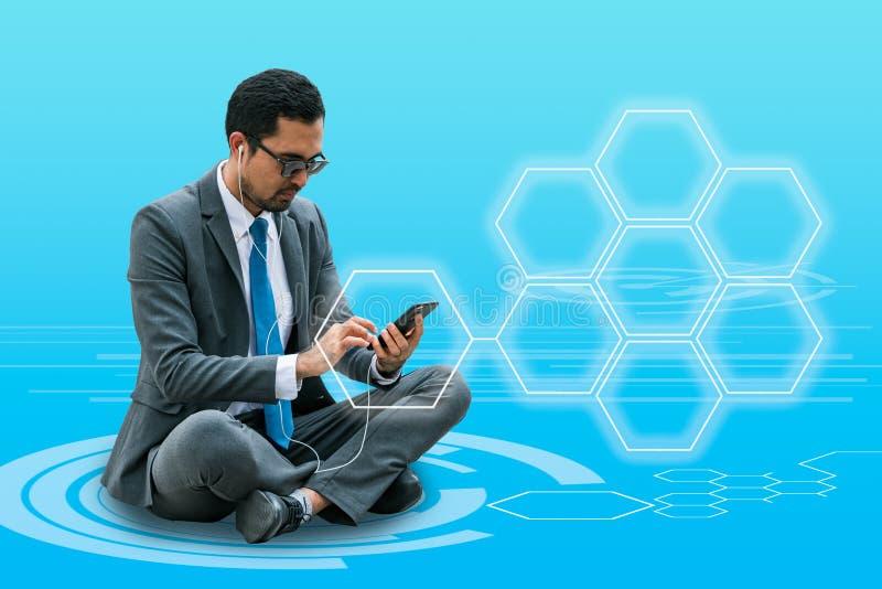 Un homme d'affaires envoyant le message du téléphone portable avec le symbole cellulaire de réseau d'hexagone images stock