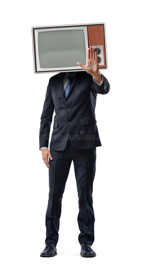 Un homme d'affaires fait un mouvement d'arrêt avec sa paume tandis qu'il utilise une boîte du vintage TV sur sa tête photographie stock