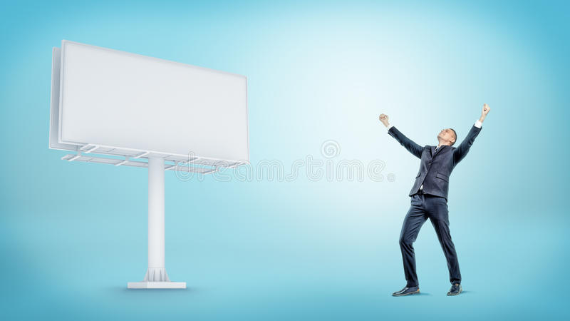 Un homme d'affaires heureux sur le fond bleu près d'un grand panneau d'affichage vide blanc photo libre de droits