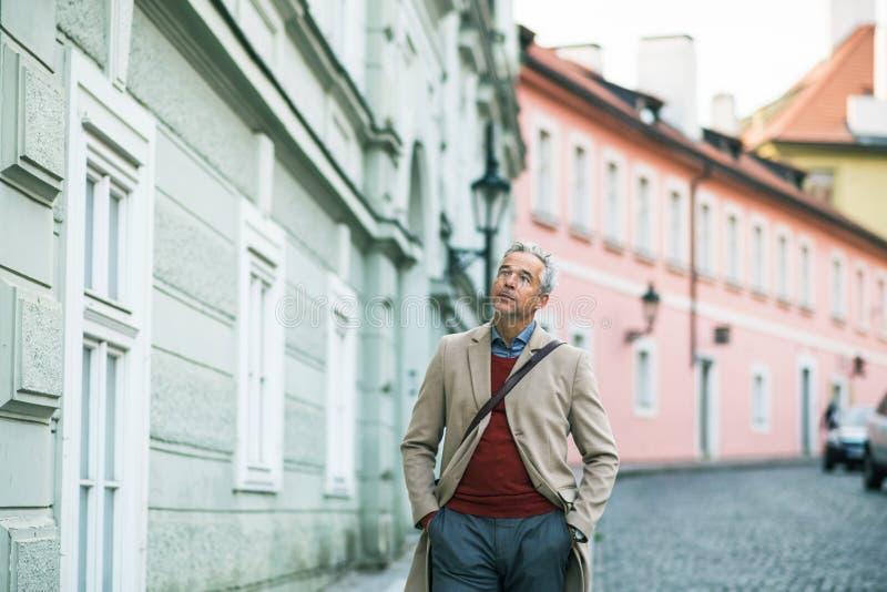 Un homme d'affaires mûr marchant sur une rue dans la ville de Prague, mains dans des poches photographie stock libre de droits