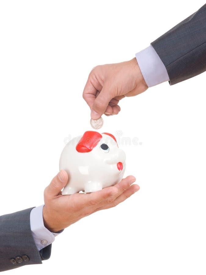 Un homme d'affaires mettant une pièce de monnaie dans une tirelire images stock