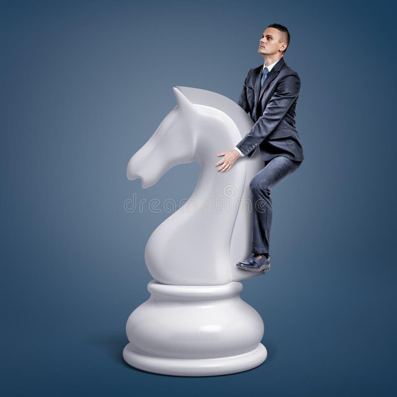 Un homme d'affaires minuscule monte un grand morceau blanc de chevalier d'échecs sur un fond bleu illustration libre de droits