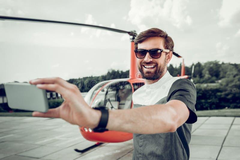 Un homme d'affaires passionnant qui fait du selfies près d'un hélicoptère privé photographie stock libre de droits