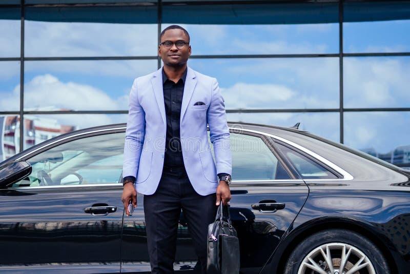 Un homme d'affaires prospère, bel homme afro-américain en costume élégant, dans une veste bleue, devant un nouveau et cool photo libre de droits