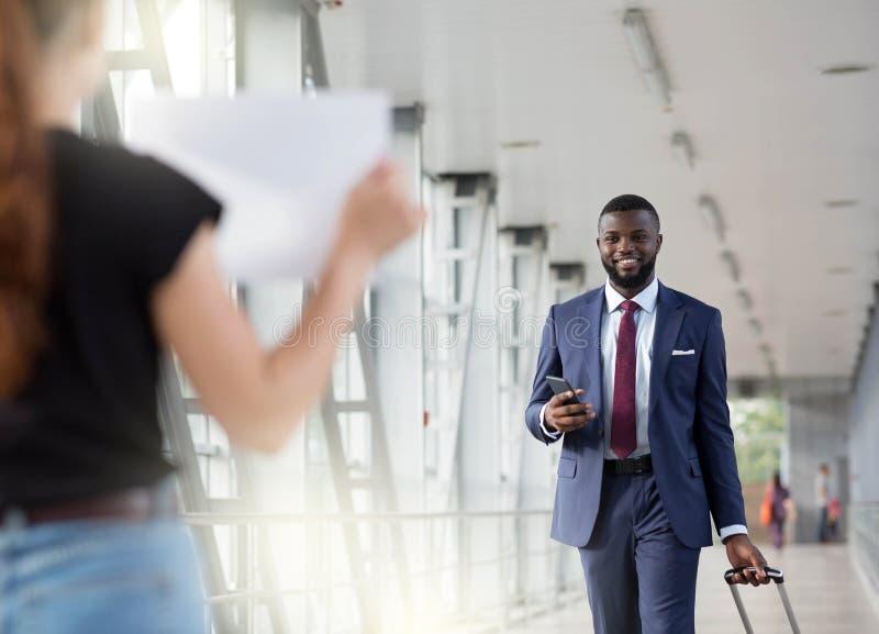 Un homme d'affaires qui agite un partenaire qui l'attend avec une pancarte sur papier photo stock