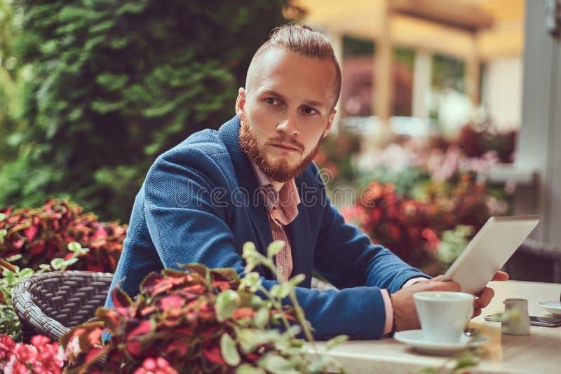 Un homme d'affaires roux bel avec une coupe de cheveux et une barbe élégantes photographie stock