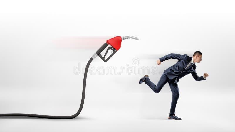 Un homme d'affaires sur le fond blanc fonctionnant à partir d'un bec de gaz rouge fixé à un tuyau noir images stock