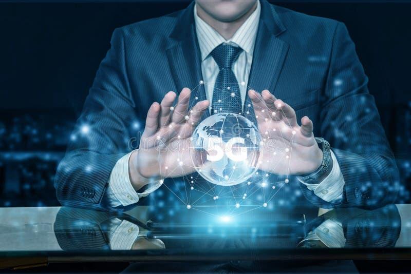 Un homme d'affaires tenant des mains au-dessus d'un globe avec le symbole 5G à l'intérieur photographie stock libre de droits