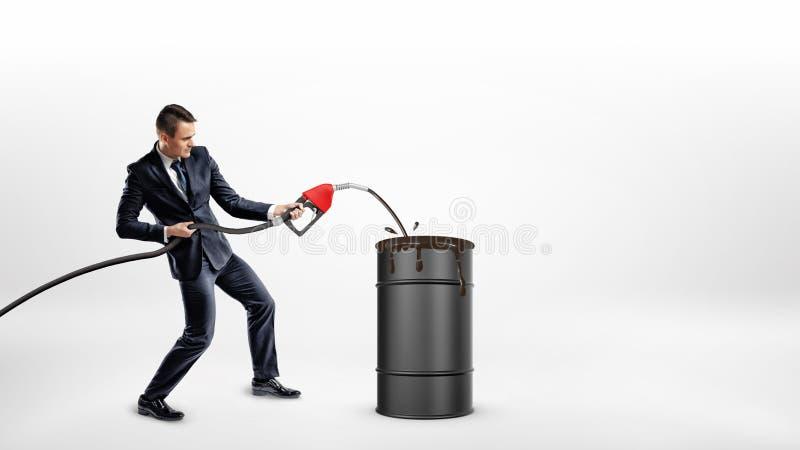 Un homme d'affaires tient un bec de gaz et remplit au-dessus du niveau un baril noir avec de l'huile image stock
