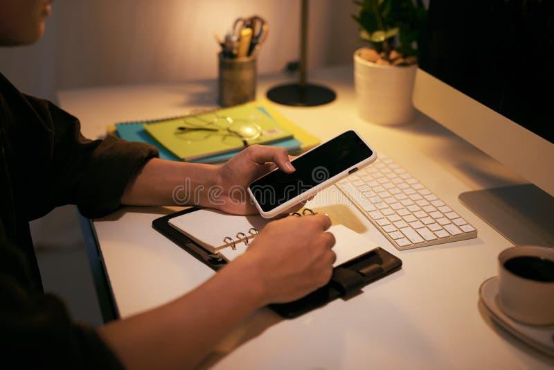 Un homme d'affaires vérifie le téléphone et écrit dans son carnet tout en se reposant à sa table de travail photos stock