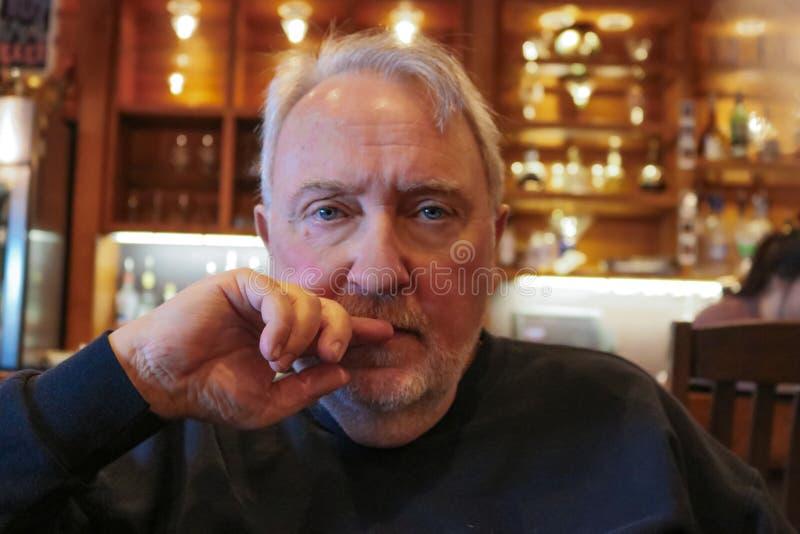 Un homme d'une chevelure gris plus âgé dans le col roulé noir se reposant au regard de table s'est inquiété avec la main de dire  images stock