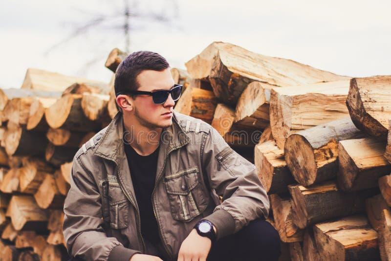 Un homme dans un équipement attrayant avec une veste moderne brune et une pose de lunettes de soleil extérieures photographie stock
