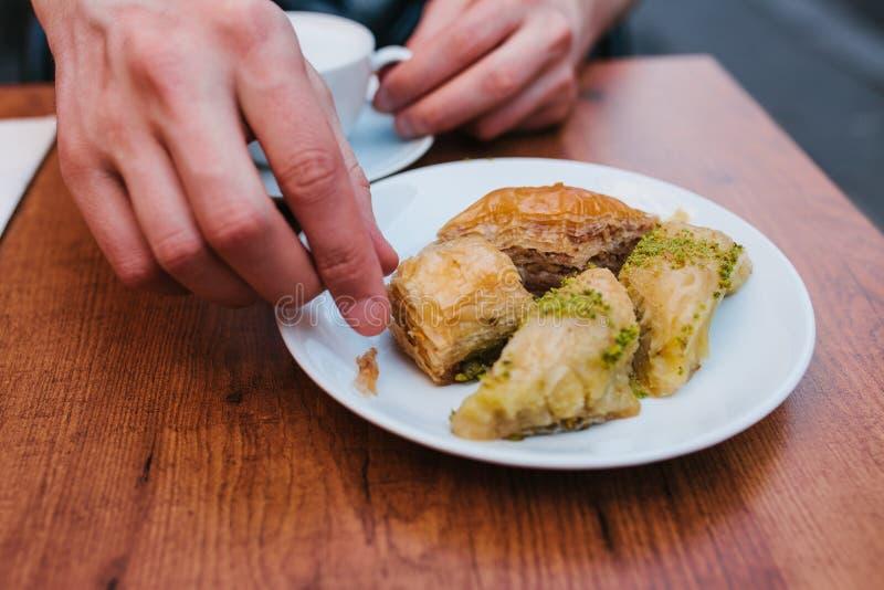 Un homme dans un café mange du café avec un dessert oriental traditionnel de baklava Nourriture orientale Dessert turc Nourriture photos stock