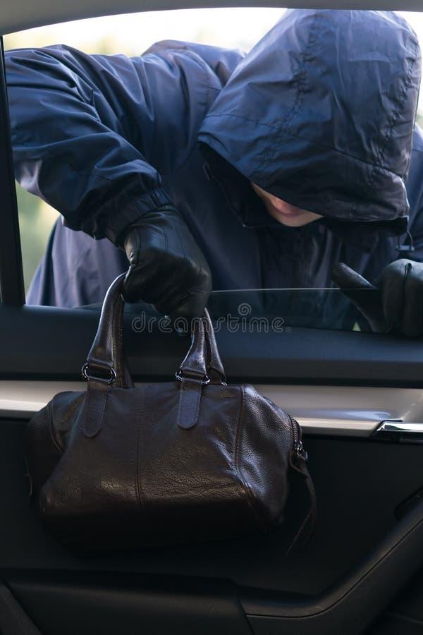 Un homme dans un capot foncé vole le sac à main d'une femme par une fenêtre de voiture photo libre de droits