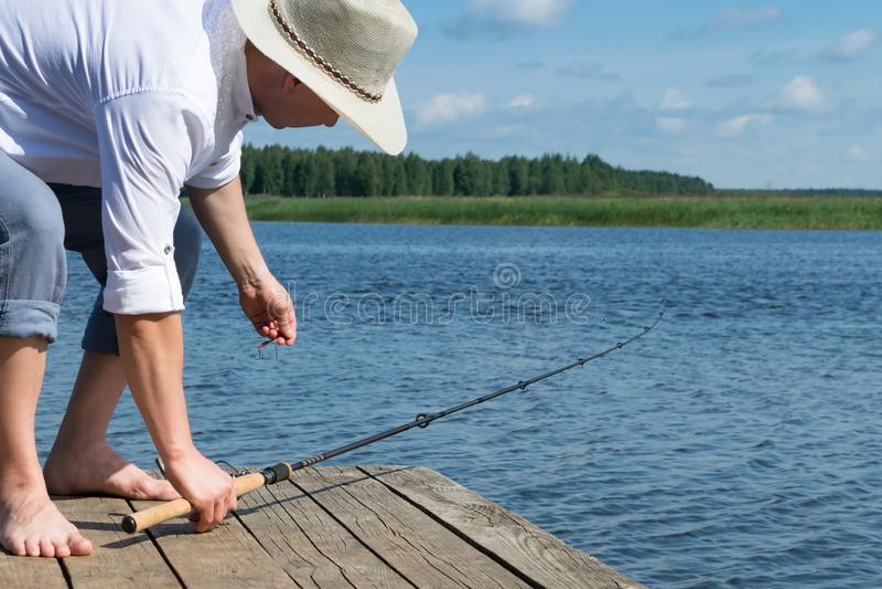 Un homme dans un chapeau prend une canne à pêche sur le fond d'un beau lac de matin photo libre de droits